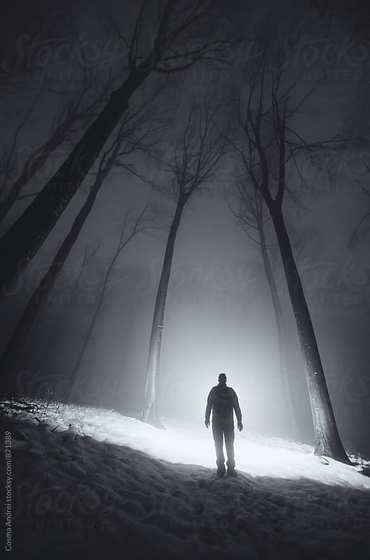 Man silhouette in surreal winter forest at night by Cosma Andrei for Stocksy United