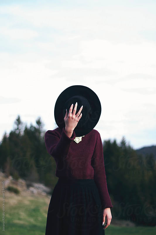 A woman hides her face behind a black hat by Jovana Rikalo for Stocksy United