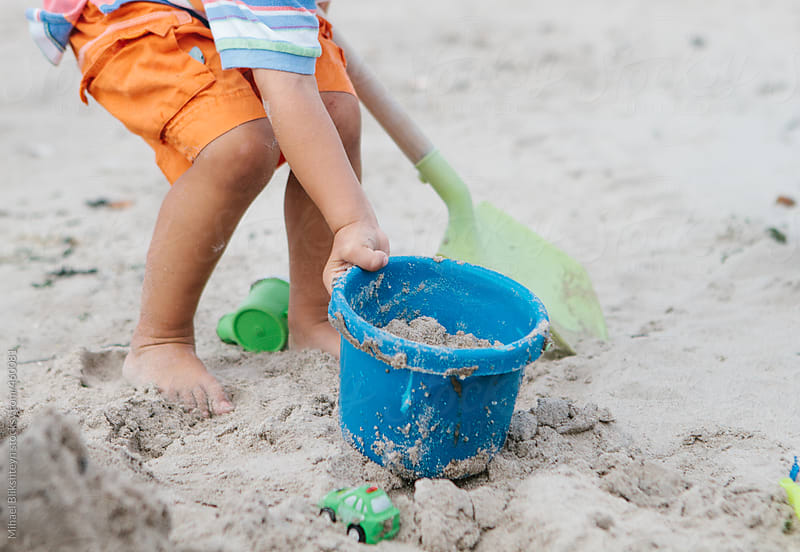 Young boy playing by himself in the sand on the beach with a bucket and shovel by Mihael Blikshteyn for Stocksy United