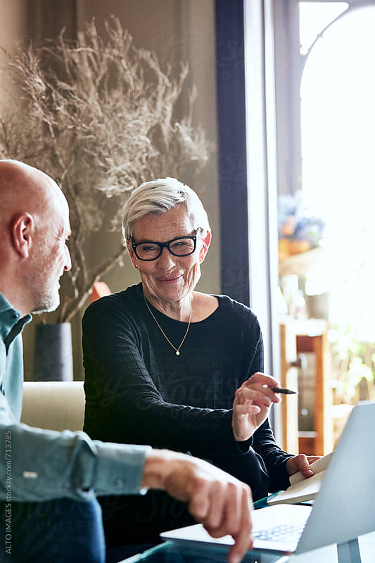 Senior Woman With Man Using Laptop In Living Room by ALTO IMAGES for Stocksy United