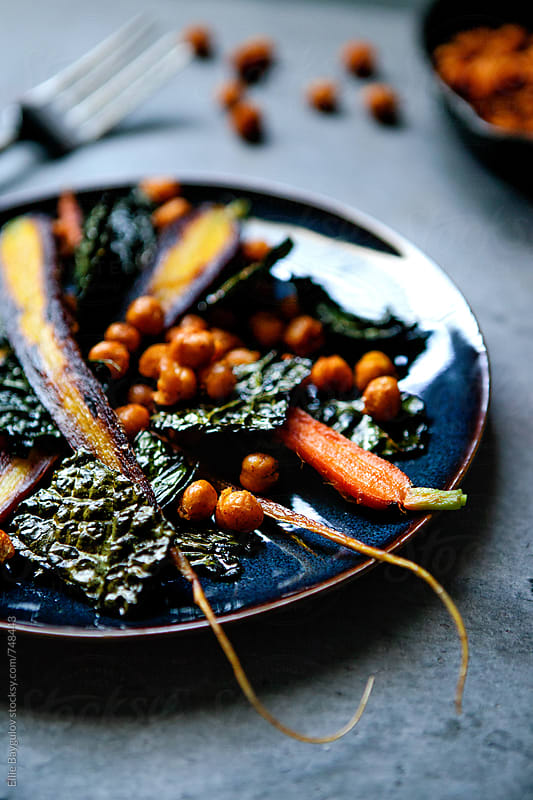 Roasted carrots and kale salad by Ellie Baygulov for Stocksy United