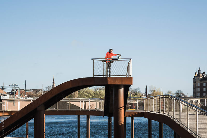 Female athlete stretching her leg on a bridge by Lior + Lone for Stocksy United