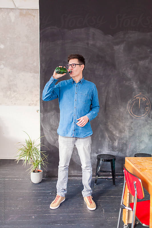 A young professional man standing in his office and taking a sip from his beer by Ivo de Bruijn for Stocksy United