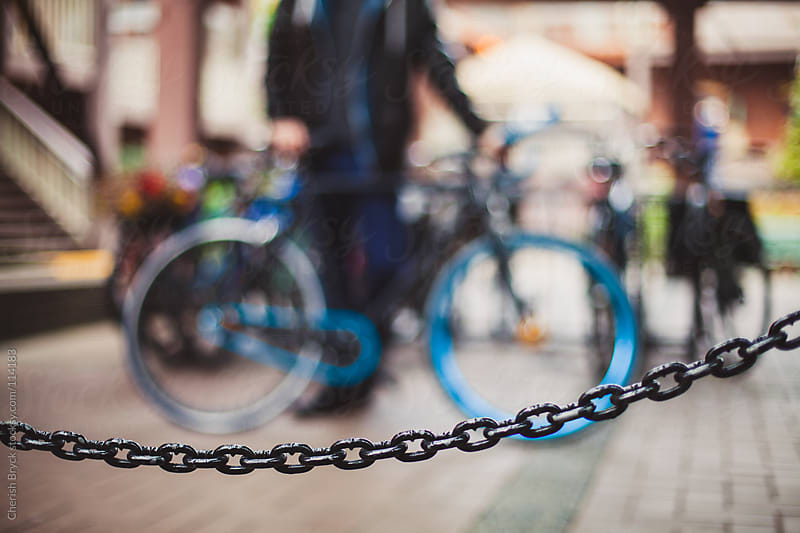 Man and his bike behind a chain link fence. by Cherish Bryck for Stocksy United