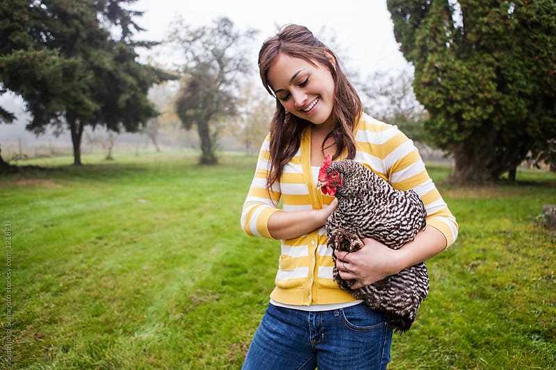 Woman carrying a chicken outside on a field by Suprijono Suharjoto for Stocksy United