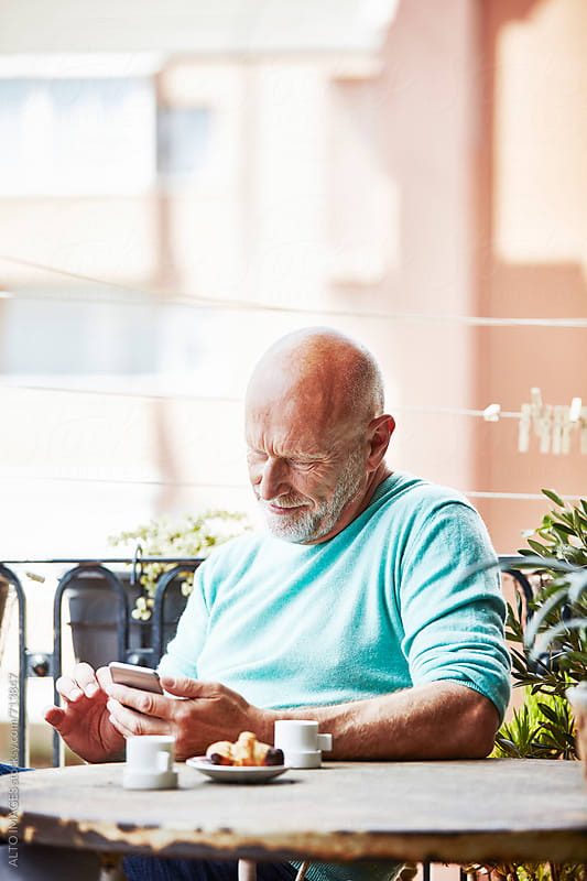 Happy Senior Man Using Smart Phone On Balcony by ALTO IMAGES for Stocksy United