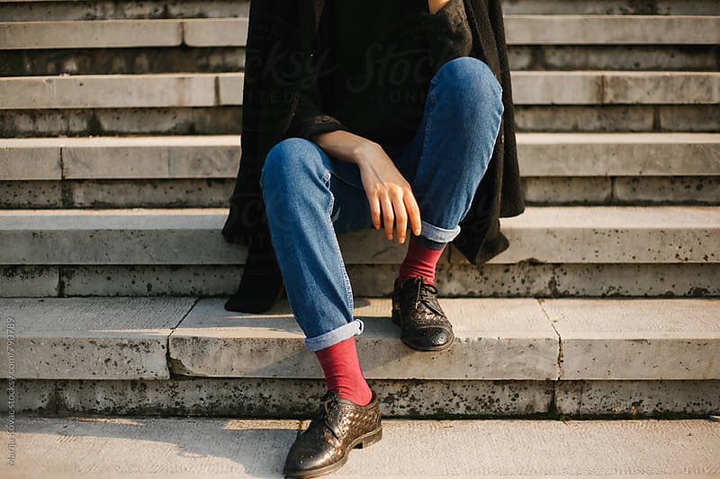 Stylish woman sitting on the stairs - just legs  by Marija Kovac for Stocksy United