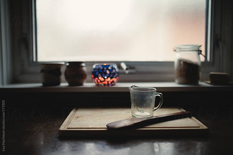 window and counter with vintage wooden spoon and antique measuring cup by Lisa MacIntosh for Stocksy United