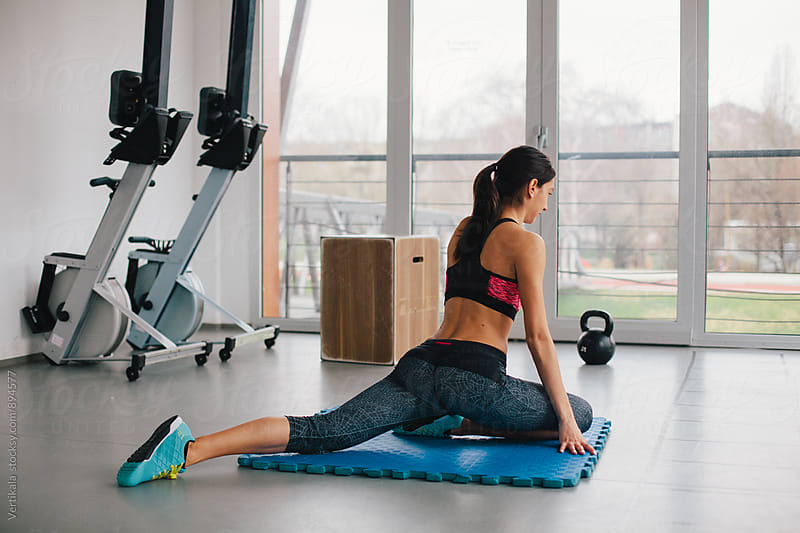 Woman doing stretching exercise in the gym  by Marija Mandic for Stocksy United