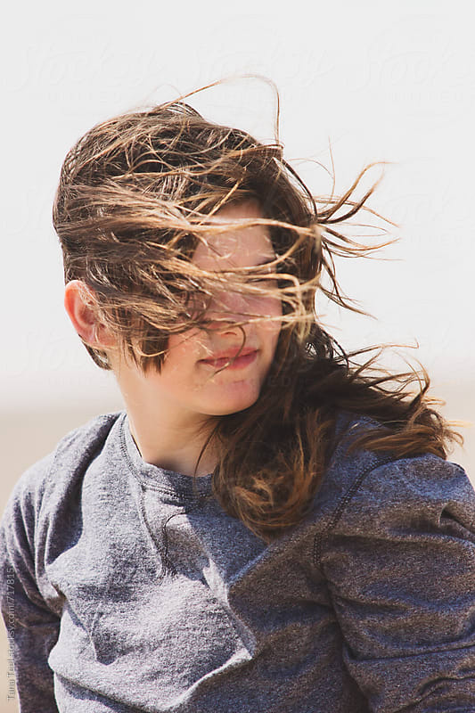 wind blowing young woman's hair by Tana Teel for Stocksy United