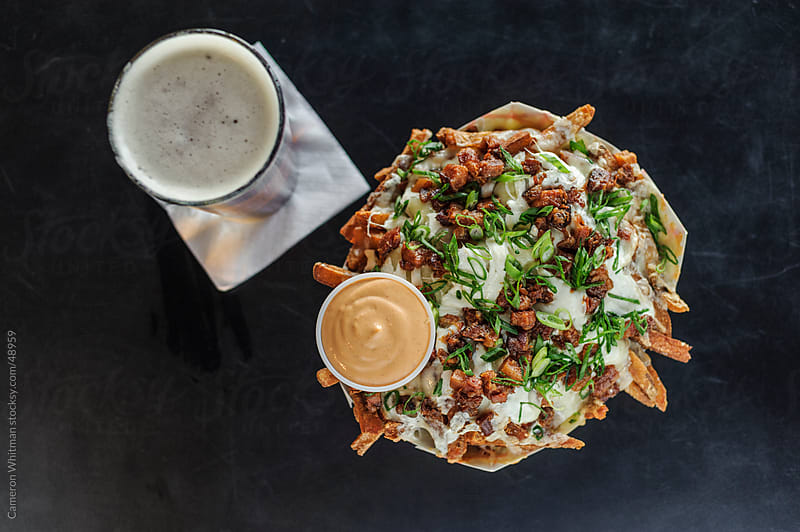 Bar Food: Cheese Fries topped with bacon and chives.  by Cameron Whitman for Stocksy United