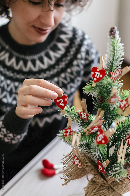 Woman decorating the Christmas tree by Davide Illini for Stocksy United