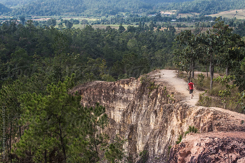 Man running down canyon trail outside in wild remote landscape. by Soren Egeberg for Stocksy United