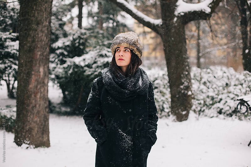 Stylish woman standing in the park during a snowy day by Marija Mandic for Stocksy United
