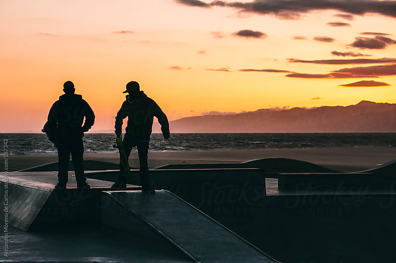 Silhouette of two skateboarders on a skatepark by the beach at sunset, Los Angeles, California by Alejandro Moreno de Carlos for Stocksy United