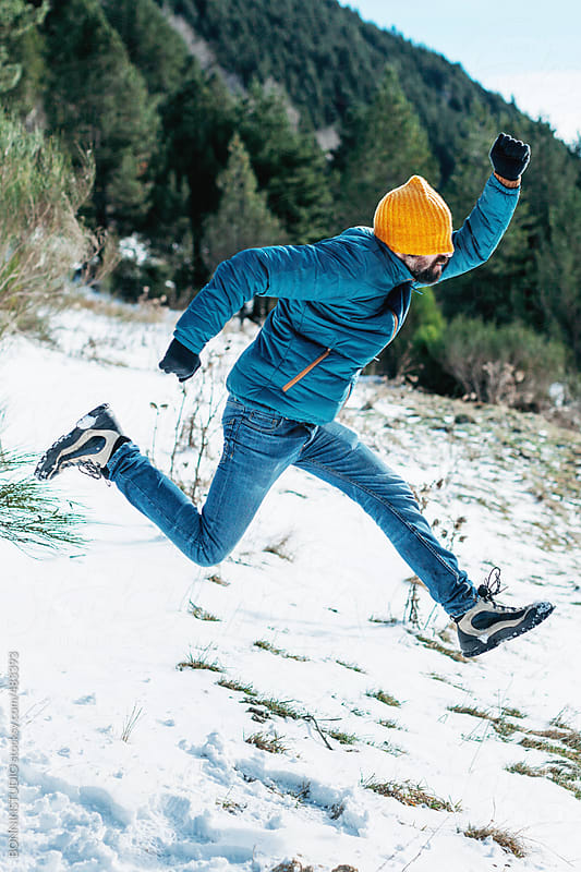 Young bearded man covered his face with yellow hat jumping on a snow landscape. by BONNINSTUDIO for Stocksy United