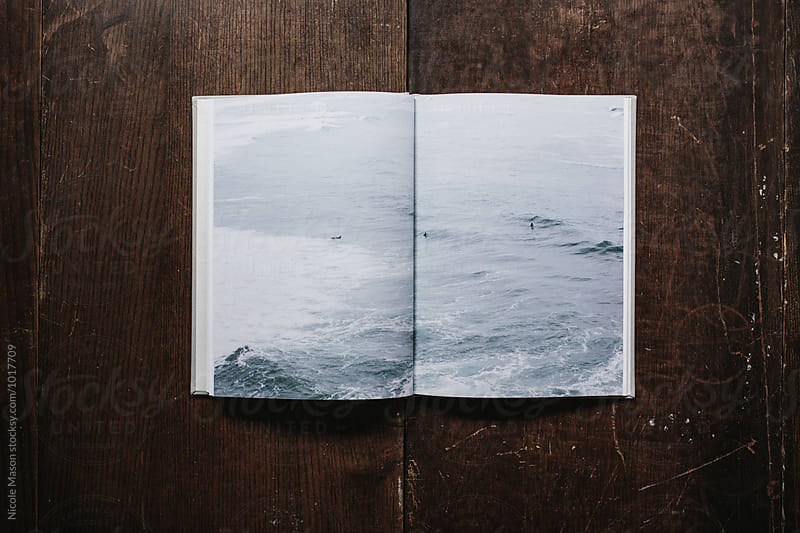 full spread image of ocean in photo book by Nicole Mason for Stocksy United