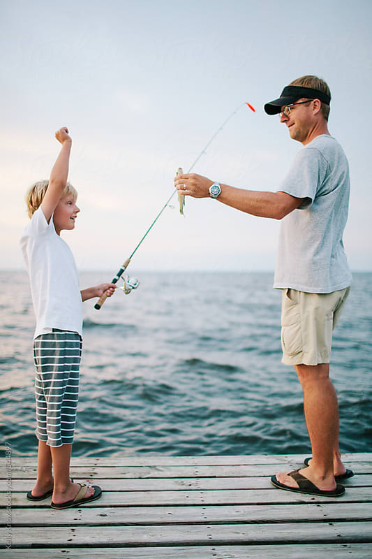 boy celebrates catching a fish with his father by Kelly Knox for Stocksy United