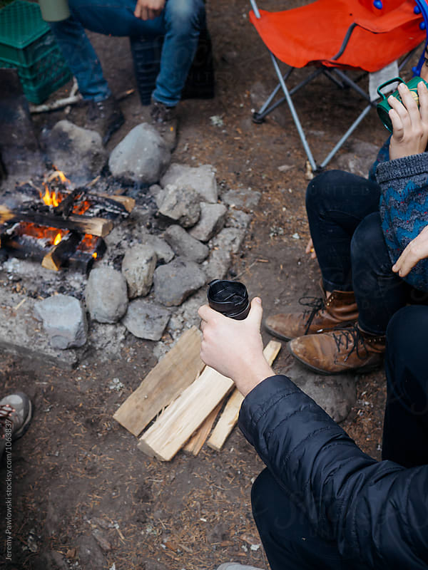 Hip group sitting outdoors around campfire with coffee and leather boots by Jeremy Pawlowski for Stocksy United