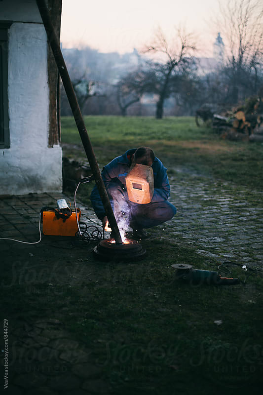 Welder welding in the garden during sunset by Marija Mandic for Stocksy United