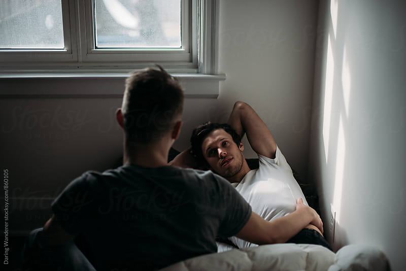 Young gay lovers in morning light lying on bed by Daring Wanderer for Stocksy United