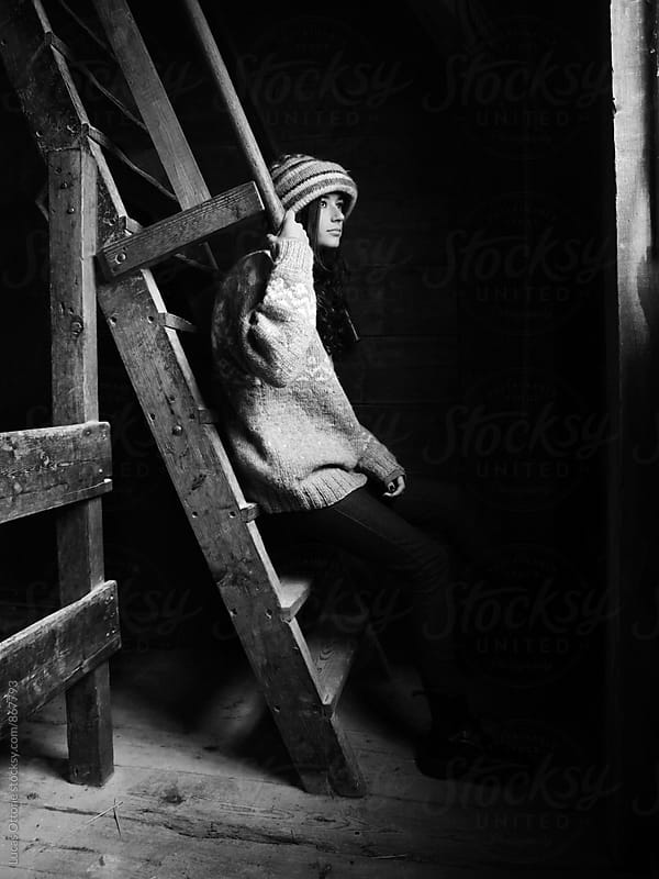 Young woman sitting on a ladder in a room in winter by Lucas Ottone for Stocksy United