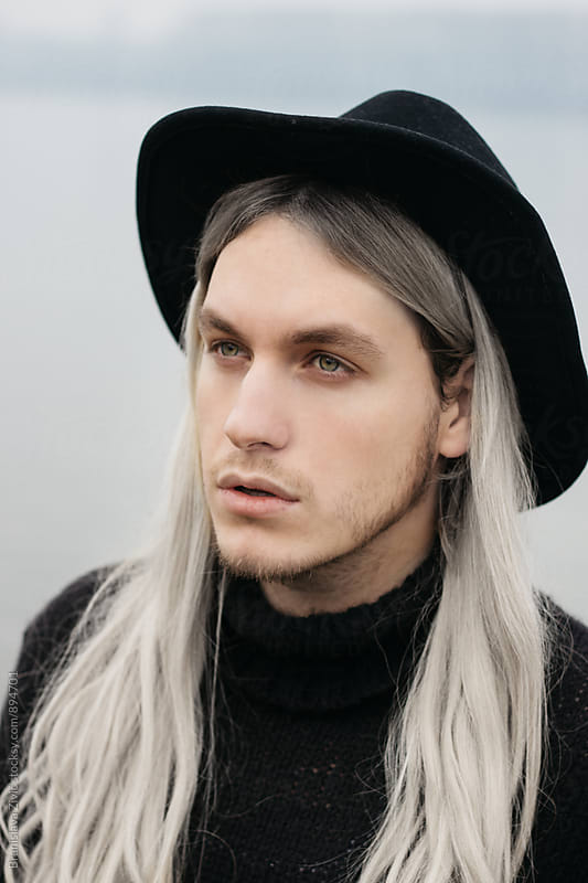 Portrait of a male model with long hair and black hat near river by Branislava Živić for Stocksy United