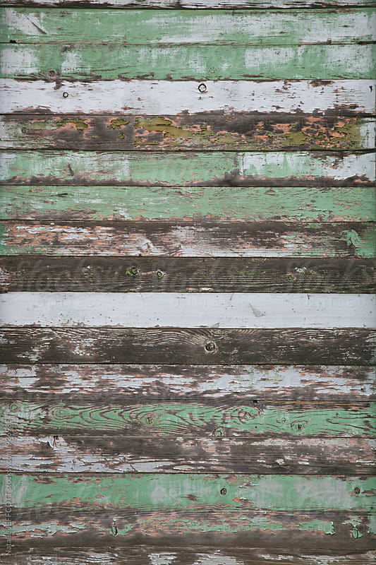 worn and weathered wooden boards with peeling shades of green paint by Natalie JEFFCOTT for Stocksy United