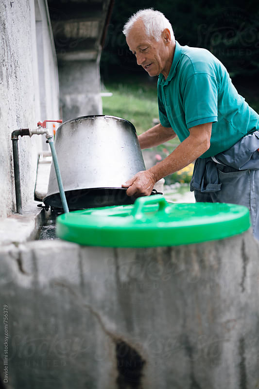 Senior man cleaning a pot by Davide Illini for Stocksy United