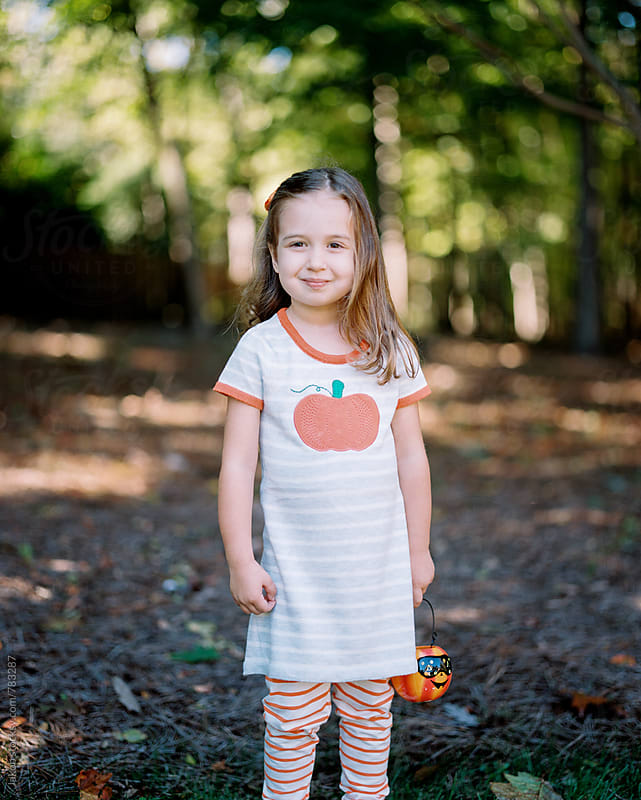 Cute girl in a pumpkin dress holding a decorative halloween pumpkin by Jakob for Stocksy United