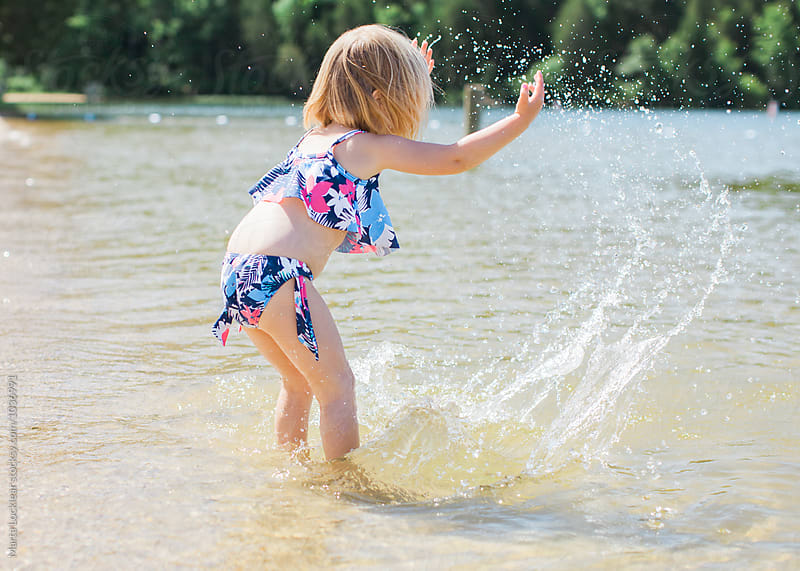 Little girl splashing in the lake water by Marta Locklear for Stocksy United