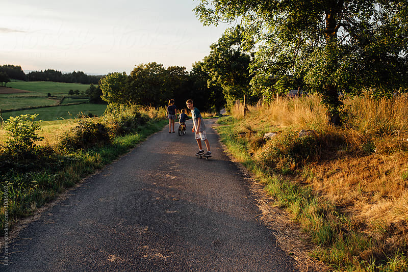 evening walk with children in countryside by Léa Jones for Stocksy United