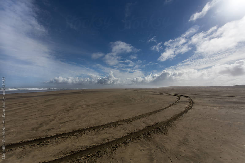 Tire tracks in the wild black sands of New Zealand by Maximilian Guy McNair MacEwan for Stocksy United