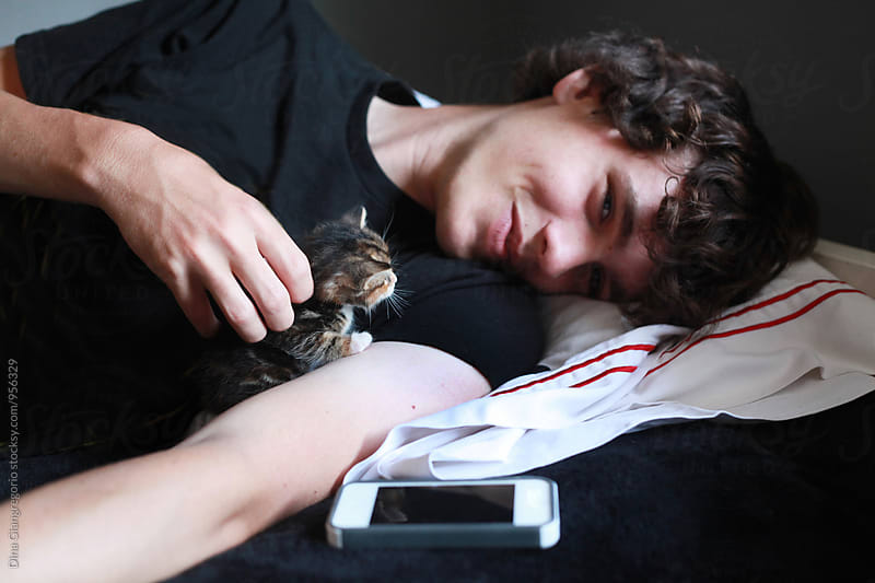Handsome Teenager Laying Down and Petting Newborn Kitten by Dina Giangregorio for Stocksy United