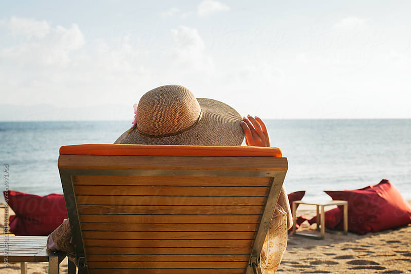 Woman Wearing Large Straw Hat Relaxing on Sunbed From Behind by Julien L. Balmer for Stocksy United