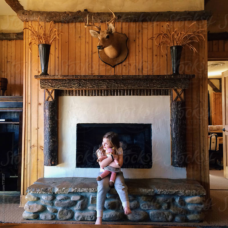 A girl hugs a stuffed animal in a lodge like setting. by Kelsey Gerhard for Stocksy United