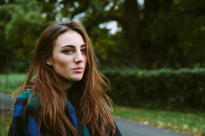 Portrait of a pretty teenage girl outdoors in the countryside by Helen Rushbrook for Stocksy United