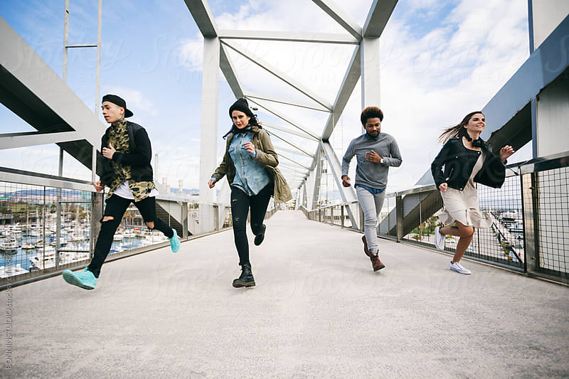 Group of friends running on a modern bridge. by BONNINSTUDIO for Stocksy United