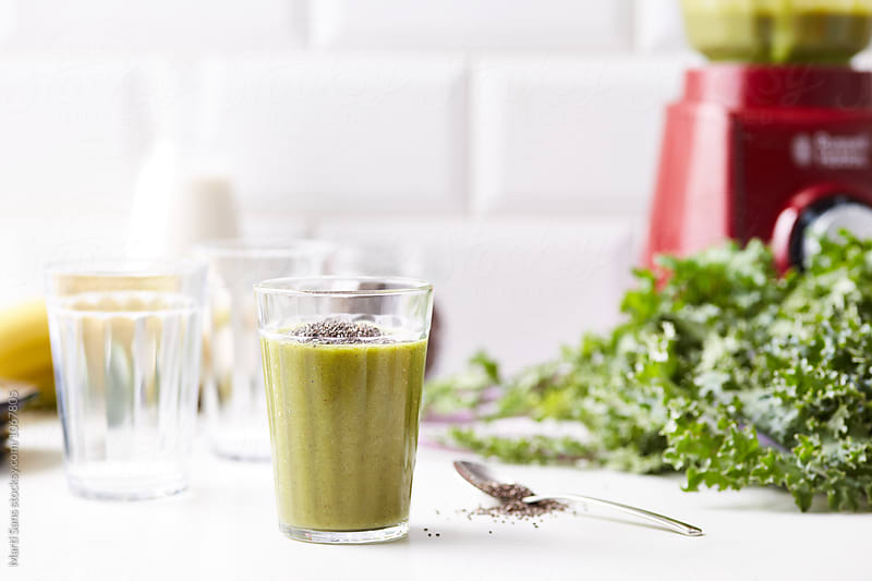Bright smoothie made with kale and fruit  by Martí Sans for Stocksy United