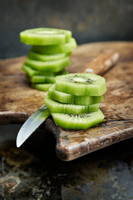 Cut kiwi fruit on a wooden chopping board by James Ross for Stocksy United