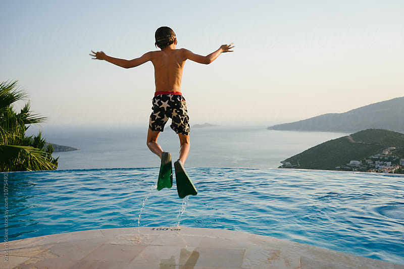 Boy jumping into pool in silly way by Kirstin Mckee for Stocksy United