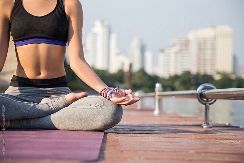 Closeup of a fit young woman meditating outdoors  by Jovo Jovanovic for Stocksy United