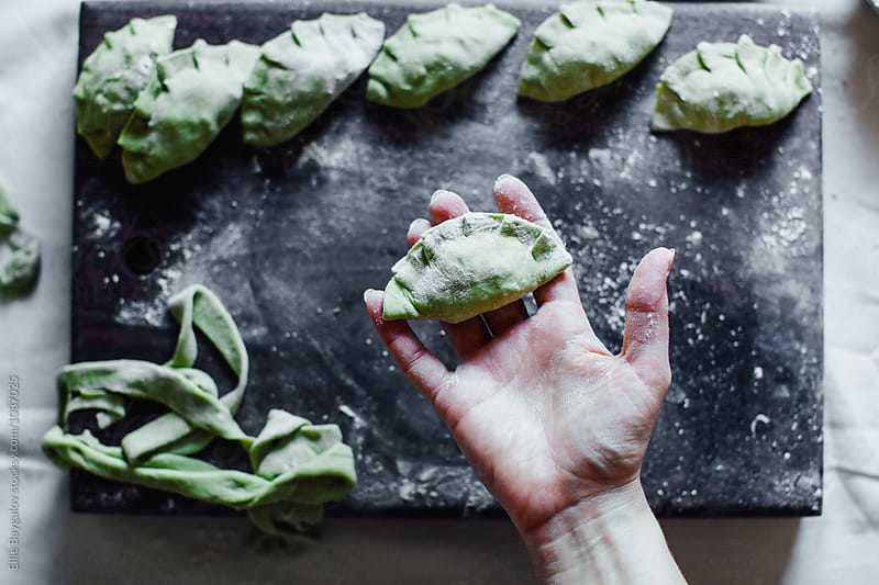 Spinach potstickers in the making by Ellie Baygulov for Stocksy United