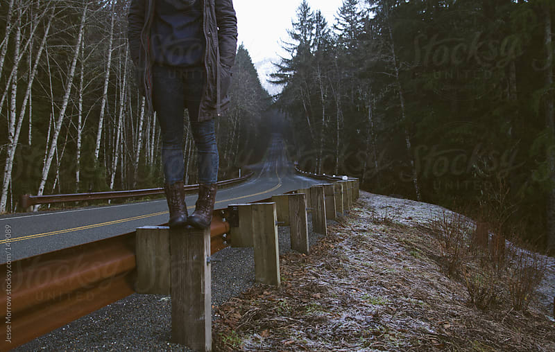 Girl stands on guard rail by Jesse Morrow for Stocksy United