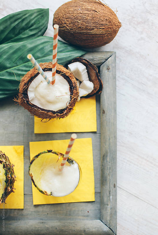 pina colada served in a glass and in a coconut from above by Leander Nardin for Stocksy United