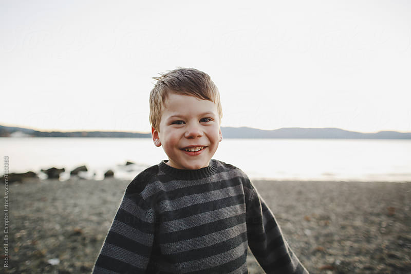 Cute young boy smiling outside near water wearing warm sweater by Rob and Julia Campbell for Stocksy United