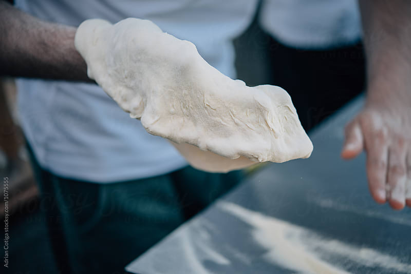 Pizza dough; Making pizza for an outdoor party by Adrian Cotiga for Stocksy United