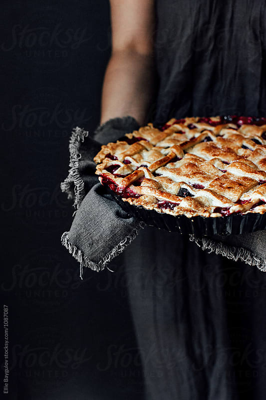 Woman holding berry pie by Ellie Baygulov for Stocksy United