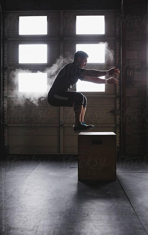 Young, fit man doing box jumps in gym by Rob and Julia Campbell for Stocksy United