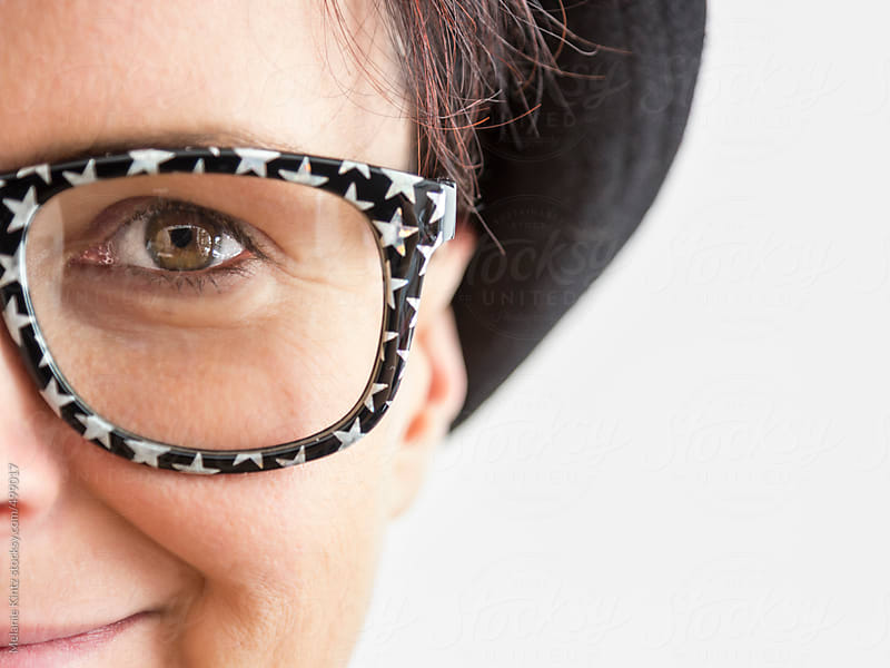 Closeup of woman with starry glasses by Melanie Kintz for Stocksy United